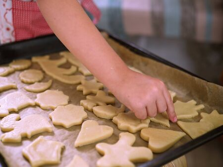 a child at home cuts out cookie cutters