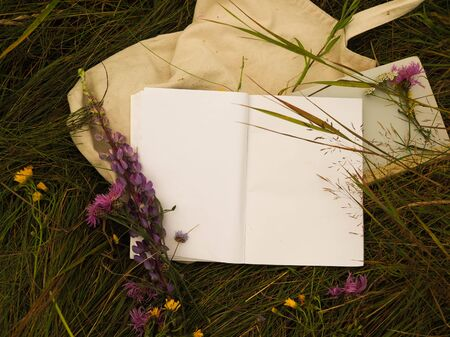 open an empty notebook on the background of grass and flowers