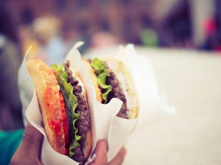 very big hamburger in his hand. fast food
