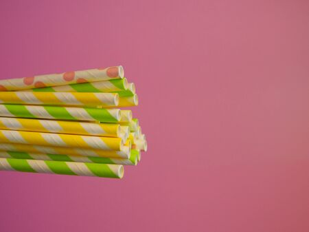 bright paper straws for a cocktail on a bright background . Summer background
