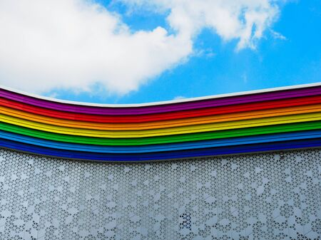 rainbow colored building and sky with clouds Stock Photo