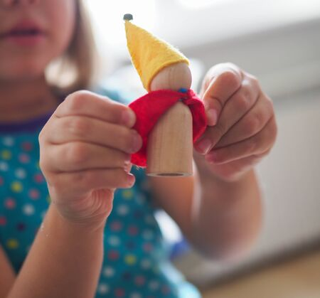 a child is holding a toy wooden gnome Standard-Bild - 138232826