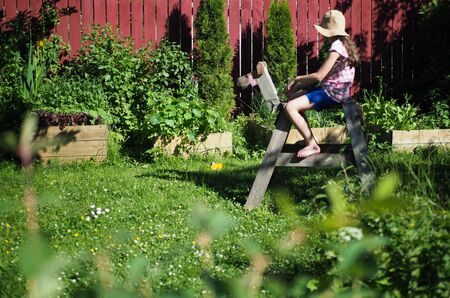 girl sitting on a wooden horse in the garden in the summer