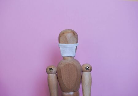 wooden mannequin in the mask from the coronavirus