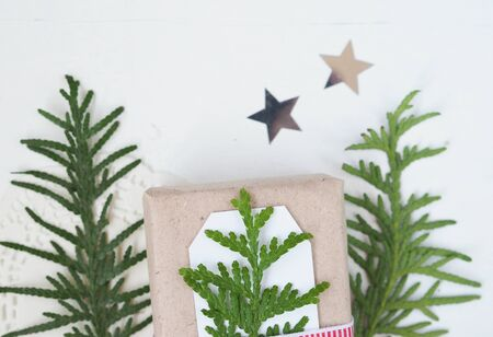 Christmas composition of spruce branches and stars on a white background minimalism
