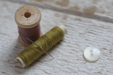 tight focus: Sewing tools on white wood background photo. Tight and blurry focus. Stock Photo