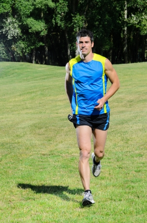 Handsome man running in summer day in park cheerful. Stock Photo - 14227466