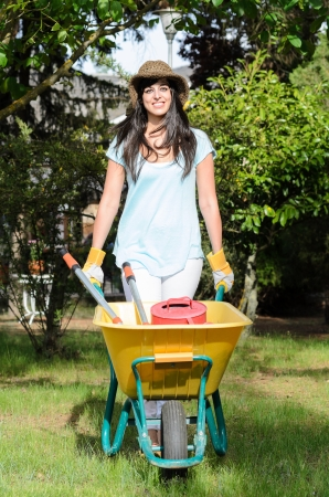 Female gardener working with wheelbarrow in garden. photo