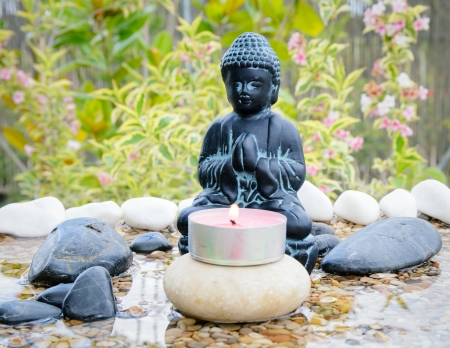 Figure of Buddha praying in a small zen pond with stones and a garden at the background.