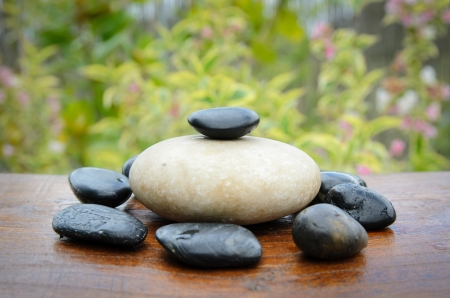 solidity: Zen stones in wood table with garden at the background.