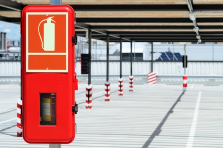 fire protection: Red extinguisher box in sunny empty parking. Stock Photo