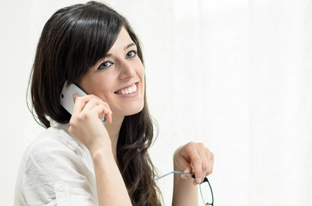 answering phone: Brunette woman using a white cellphone and smiling.