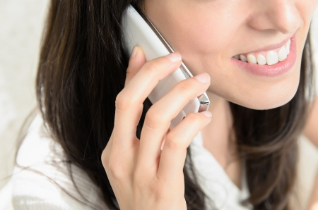 Close-up of a beautiful young woman talking on mobile phone intimately and smiling photo