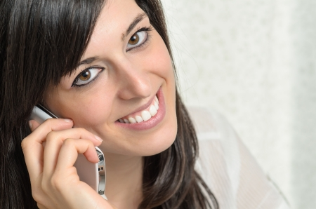 intimately: beautiful young woman talking on mobile phone intimately Stock Photo