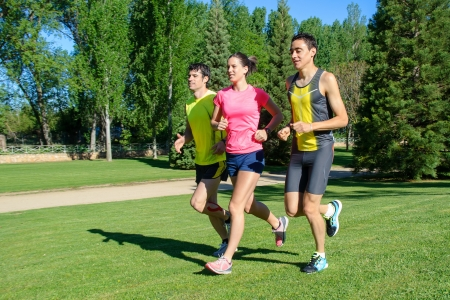 sportwoman: Young cheerful people training in a park during a summer day