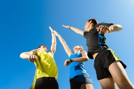 Squadra giovane con due uomini e donna, fiving e saltare per celebrare la vittoria ei risultati Archivio Fotografico