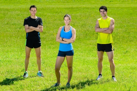 sportwoman: Young athletes looking at camera with grass background