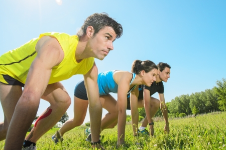 vigor: Group of runners ready to go in a challenge outdoors