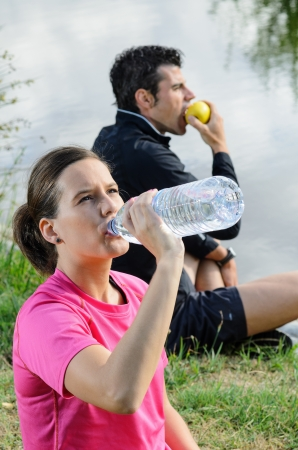 A healthy couple drinking water and eating apple for recovering after training. photo