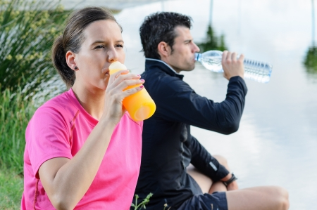 thirstiness: Young athletes sitting and drinking water and isotonic drink for recovering from trainning.