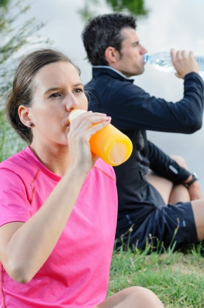 thirstiness: Young couple of athletes sitting and drinking water and oranje juice for recovering from trainning. Stock Photo