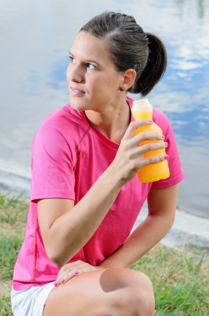 thirstiness: Young female athlete drinking isotonic drink for rehydratation and recover nutrients  Stock Photo