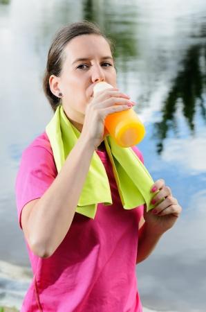 nutrientes: Joven atleta de sexo femenino bebida isot�nica para beber rehidrataci�n y recuperaci�n de nutrientes