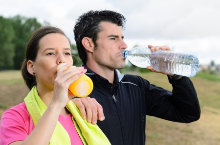 thirstiness: Young sport couple drinking water and isotonic drink after trainning