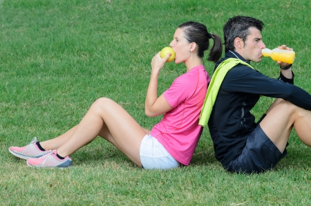 thirstiness: Couple of athletes taking a break, eating an apple and drinking isotonic drink  Stock Photo