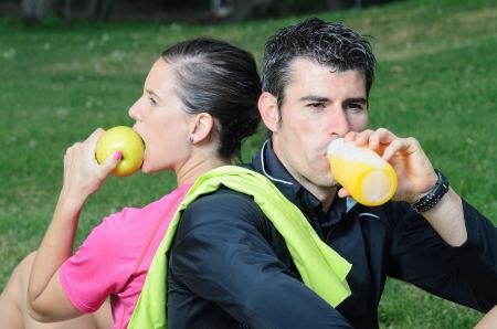 rehydration: Couple of athletes taking a break, eating an apple and drinking isotonic drink  Stock Photo
