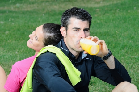 Couple of happy athletes taking a break, and smiling while the male drinks orange juice and women rests on the man photo