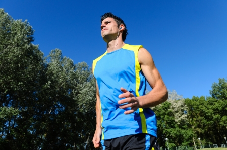 Handsome man running in park with earphones. Stock Photo - 14301106