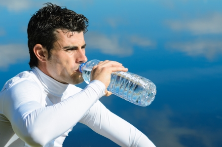 thirstiness: Handsome sportman drinking water on a break with water reflections in background.