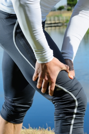 muscle pain: Sportsman feels muscle pain and grabs the leg. Stock Photo