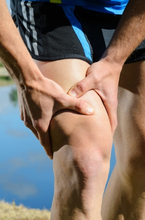 Runner feels muscle pain and grabs the leg. photo