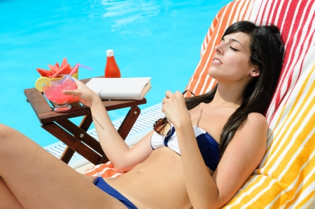 Woman enjoying with drink ath the poolside . She is sunbathing and relaxing with a book and fruit in a table. photo