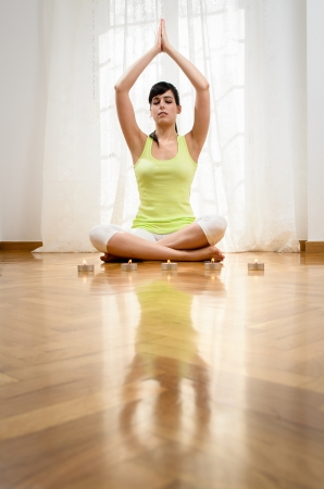 Beautiful young woman doing yoga exercise and meditating at home. photo