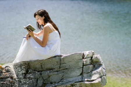 peacefulness: Woman reading a book in nature with water background.