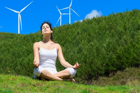 Women enjoy the outdoors in nature, relaxing with windmills in the background Stock Photo - 14301101