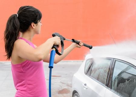 water gun: Woman washing car with water gun  Stock Photo
