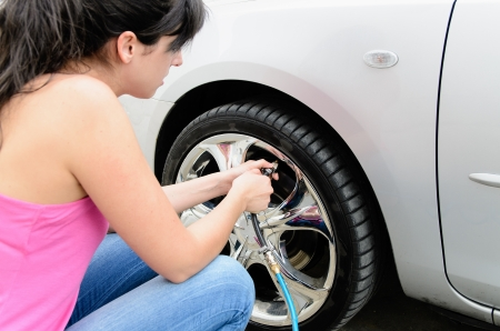 inflating: Young woman checking pressure and inflating car tires