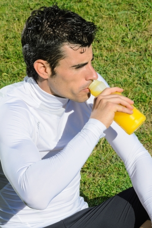recover: Sportsman resting and drinking  to recover sugar , mineral salts and energy with an isotonic drink
