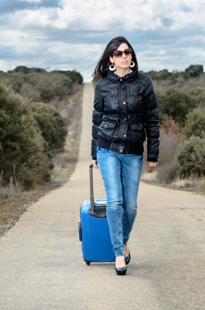 getting away from it all: Woman with jeans walking in lonely road with a blue suitcase in a cloudy day  Stock Photo