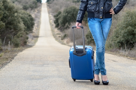 Detail of the legs of  a woman waiting in a lonely road with blue suitcase  Stock Photo - 14301107