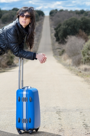 A beautiful young brunette woman is leaning on a blue suitcase in the middle of a road, waiting  photo