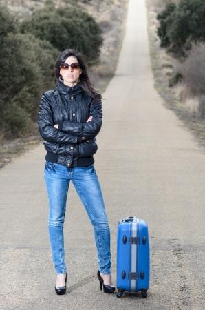 mujer con maleta: Mujer con pantalones vaqueros esperando de brazos cruzados en una carretera solitaria con una chaqueta azul suitcaseand negro