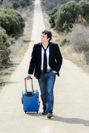 runaway: Handsome man walking in a lonely road with suitcase  Stock Photo