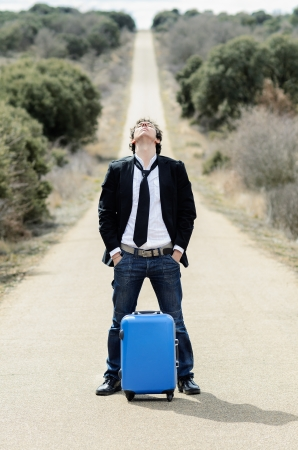 getting away from it all: Handsome man symbolizes freedom waiting with hands in pockets in a lonely road with suitcase