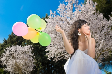 joy of life: Young beautiful woman playing with colorful balloons, smiling and celebrating love and life in a spring scene