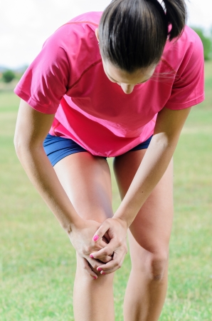 muscle woman: Female athlete suffer from pain in her knee